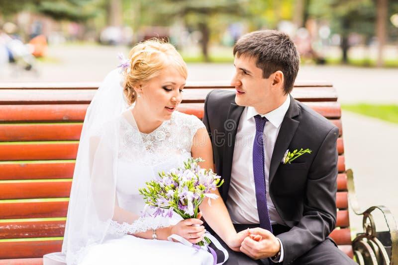 Los pares en la boda attire con un ramo de flores, de novia y de novio al aire libre fotografía de archivo libre de regalías