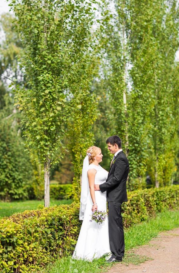 Los pares en la boda attire con un ramo de flores, de novia y de novio al aire libre fotos de archivo libres de regalías