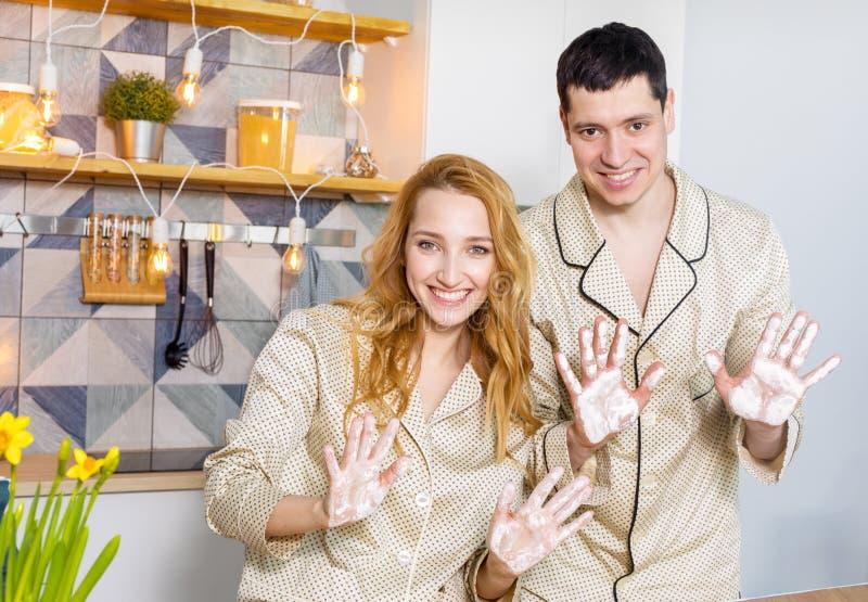 Los pares en la cocina muestran las manos en harina foto de archivo libre de regalías