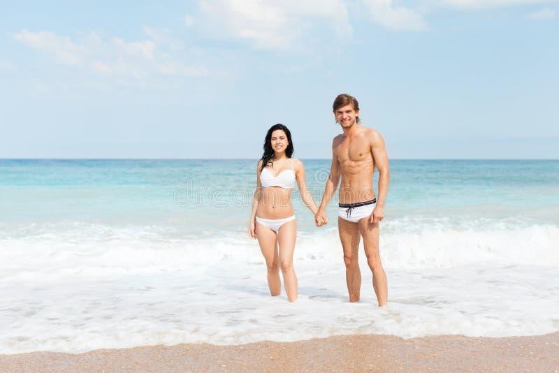 Los pares en la playa que se coloca en onda de agua hacen espuma foto de archivo