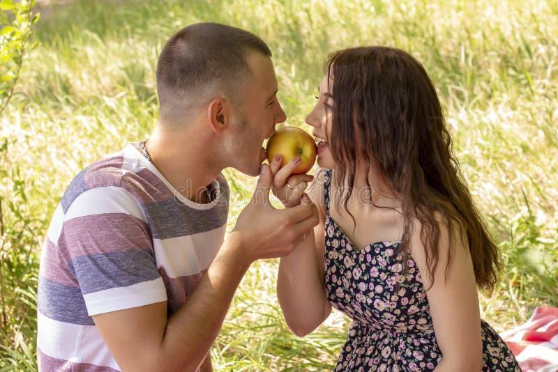 Los pares en muchacho y muchacha del amor comen aire libre de la comida campestre del verano de la manzana imagen de archivo