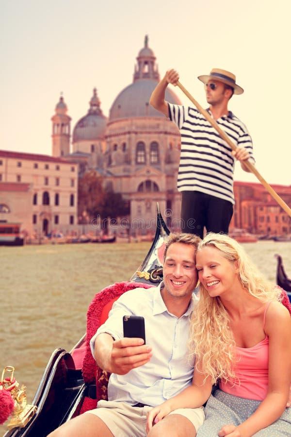 Los pares en Venecia en la góndola montan en el canal grande imagenes de archivo