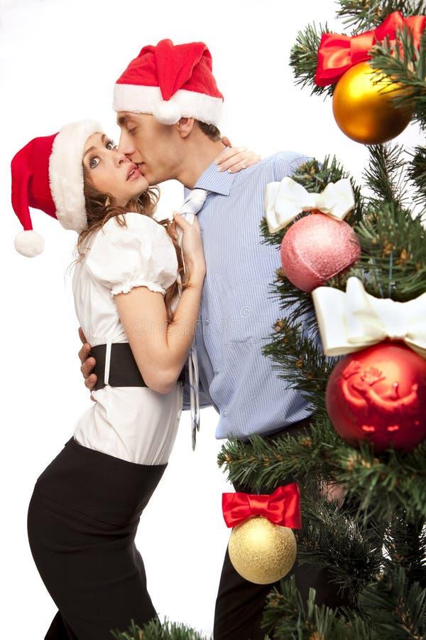 Los pares encantadores acercan a un árbol de navidad foto de archivo libre de regalías
