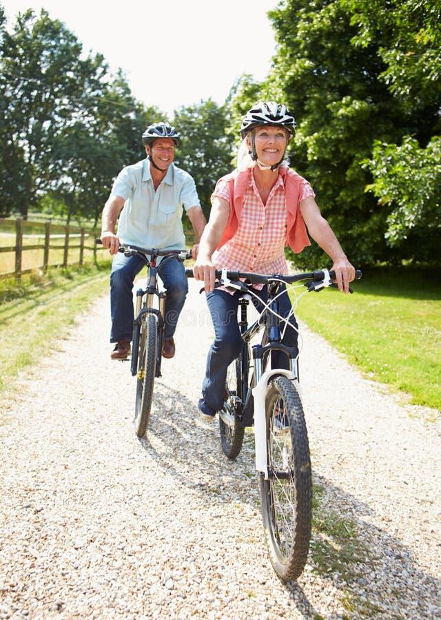 Los pares envejecidos centro que disfrutan del ciclo del país montan juntos imagenes de archivo