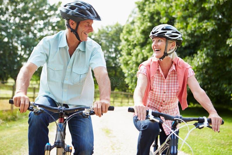 Los pares envejecidos centro que disfrutan del ciclo del país montan juntos fotografía de archivo libre de regalías