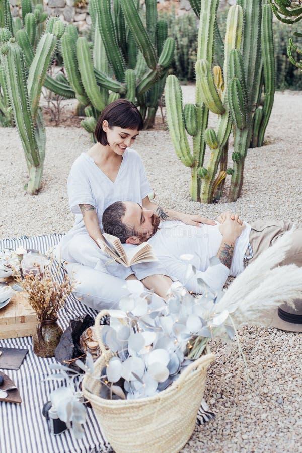 Los pares fecha romántica ponen en la manta de la comida campestre imagen de archivo libre de regalías