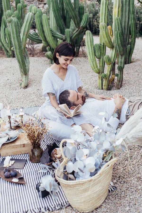 Los pares fecha romántica ponen en la manta de la comida campestre foto de archivo