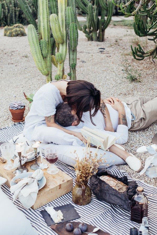 Los pares fecha romántica ponen en la manta de la comida campestre fotos de archivo