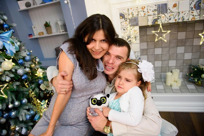 Los pares felices de la familia dan los regalos en la sala de estar, detrás del árbol de navidad adornado, la luz para dar una at imagenes de archivo