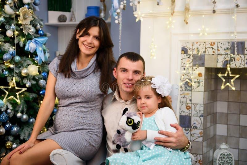 Los pares felices de la familia dan los regalos en la sala de estar, detrás del árbol de navidad adornado, la luz para dar una at imágenes de archivo libres de regalías