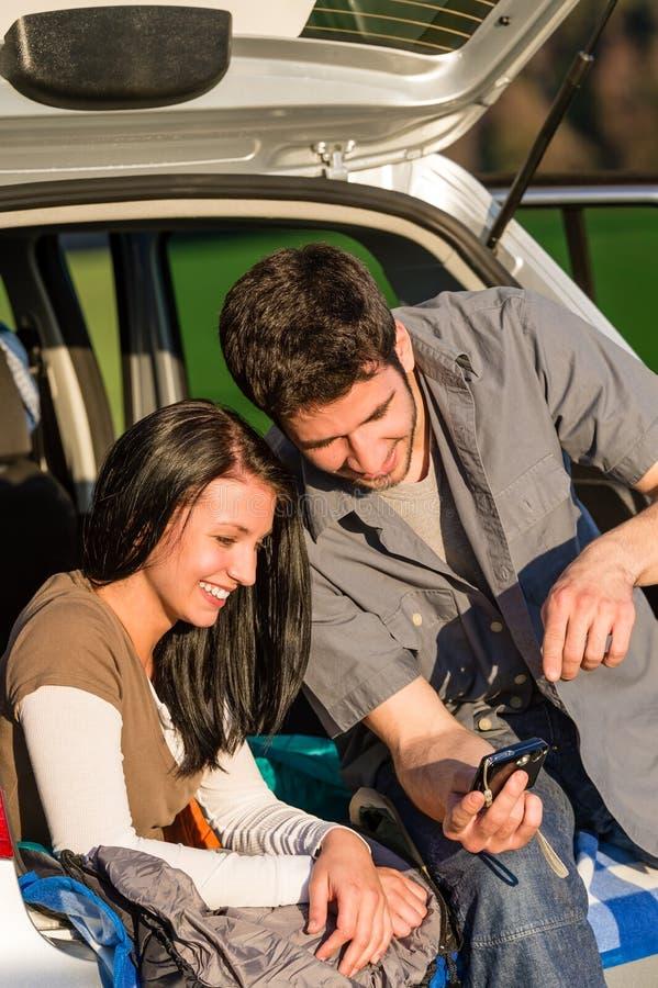 Los pares felices del coche que acampa miran puesta del sol de la cámara fotos de archivo libres de regalías