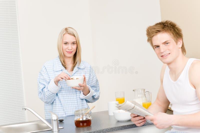 Los pares felices del desayuno comen el periódico leído cereal fotos de archivo
