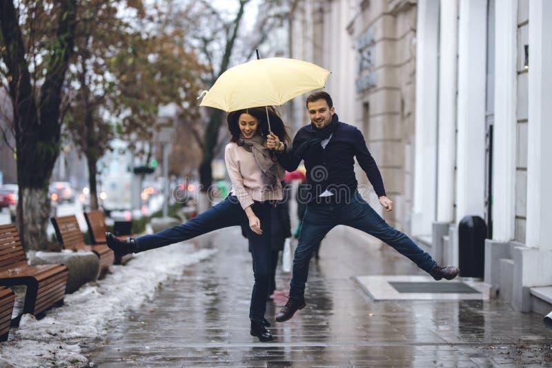 Los pares felices, el individuo y su novia vestidos en ropa casual est?n saltando debajo del paraguas en la calle bajo la lluvia imagenes de archivo