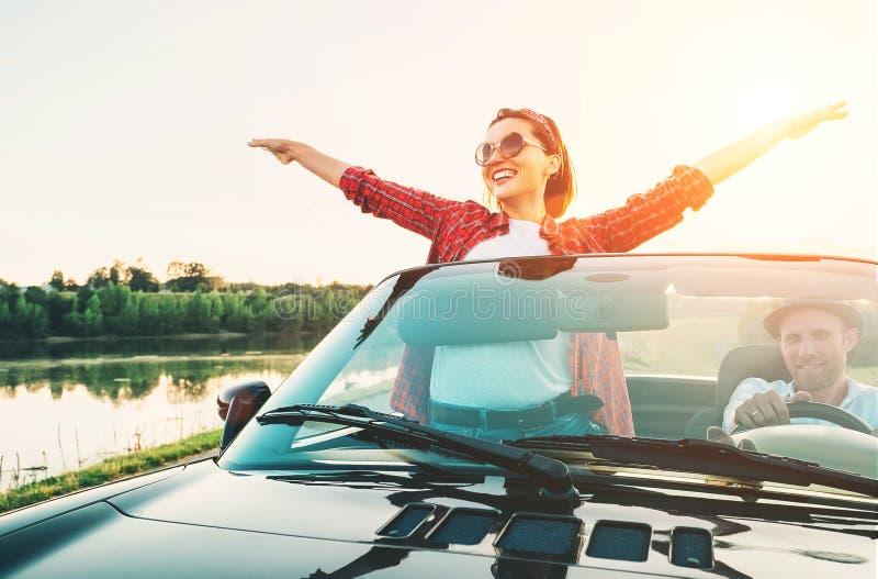 Los pares felices en amor van en coche del cabriolé en tiempo de la puesta del sol imágenes de archivo libres de regalías