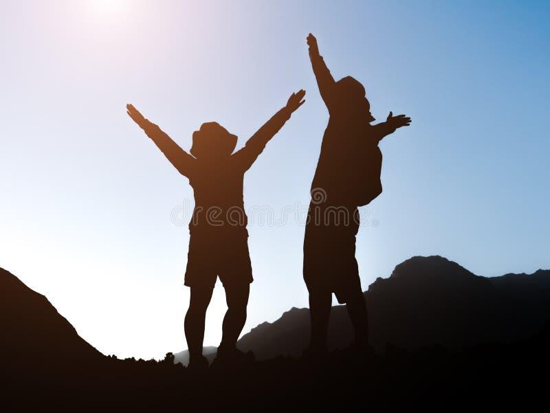 Los pares felices en cordillera están mirando paisaje de la puesta del sol foto de archivo