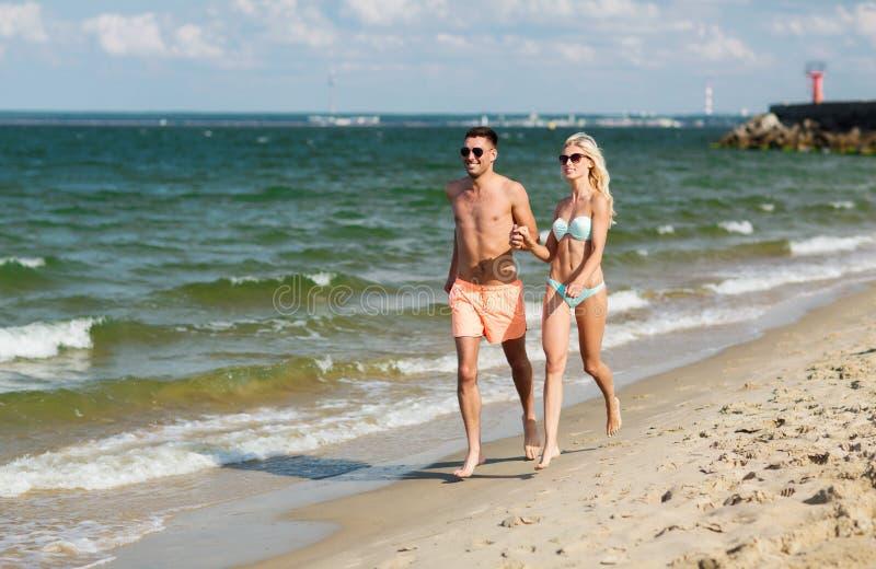 Los pares felices en el traje de baño que corre el verano varan fotos de archivo libres de regalías