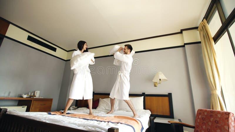 Los pares felices jovenes en albornoz luchan las almohadas y se divierten en cama en hotel durante sus vacaciones de la luna de m fotos de archivo