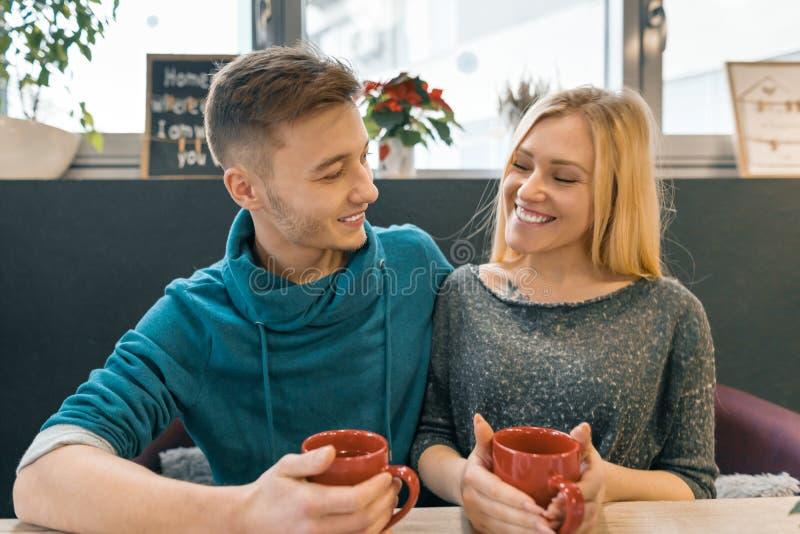Los pares felices jovenes en amor en café, hombre joven y mujer juntos sonríen abrazando té del café de la bebida fotos de archivo libres de regalías