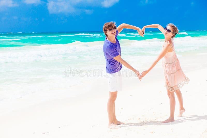 Los pares felices jovenes en la luna de miel que hace el corazón forman fotos de archivo libres de regalías