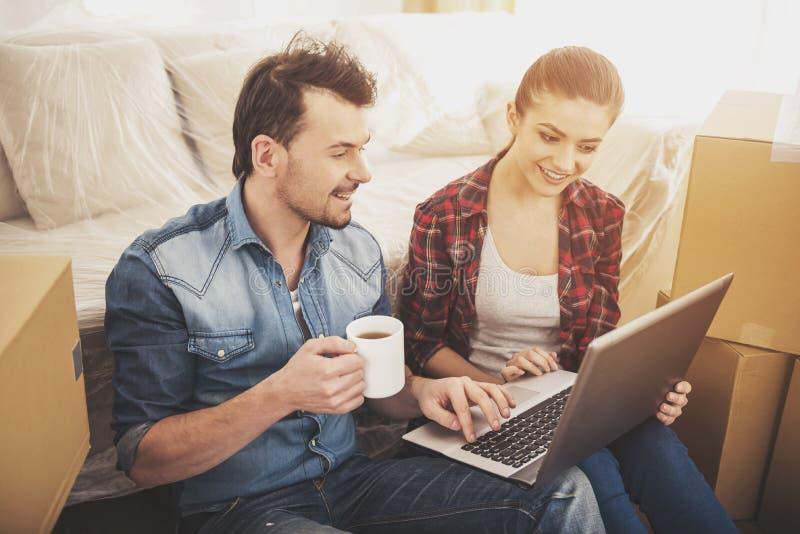 Los pares felices jovenes que buscan para los apartamentos con el ordenador portátil Mudanza, compra de la nueva habitación imagenes de archivo