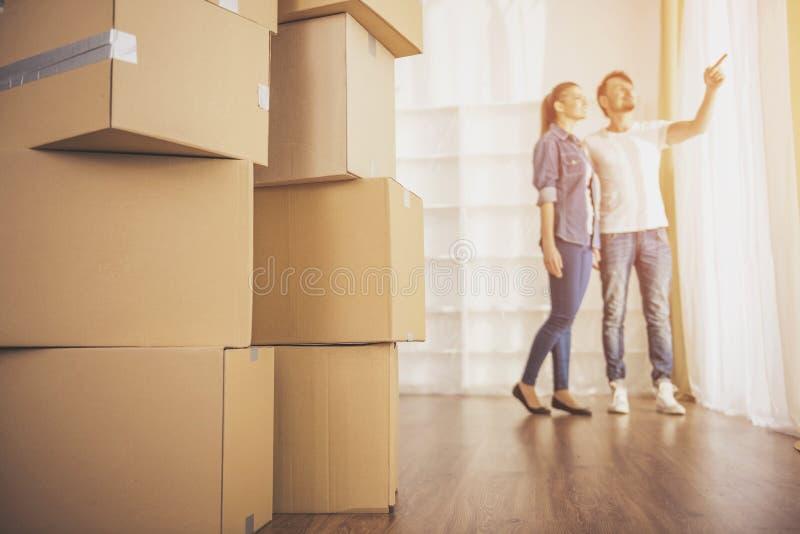 Los pares felices jovenes que miran alrededor de su nuevo apartamento Mudanza, compra de la nueva habitación fotos de archivo libres de regalías