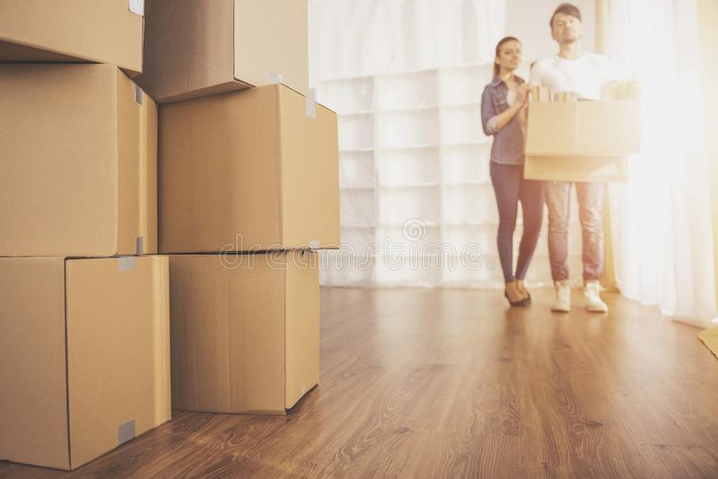 Los pares felices jovenes que miran alrededor de su nuevo apartamento Mudanza, compra de la nueva habitación fotografía de archivo