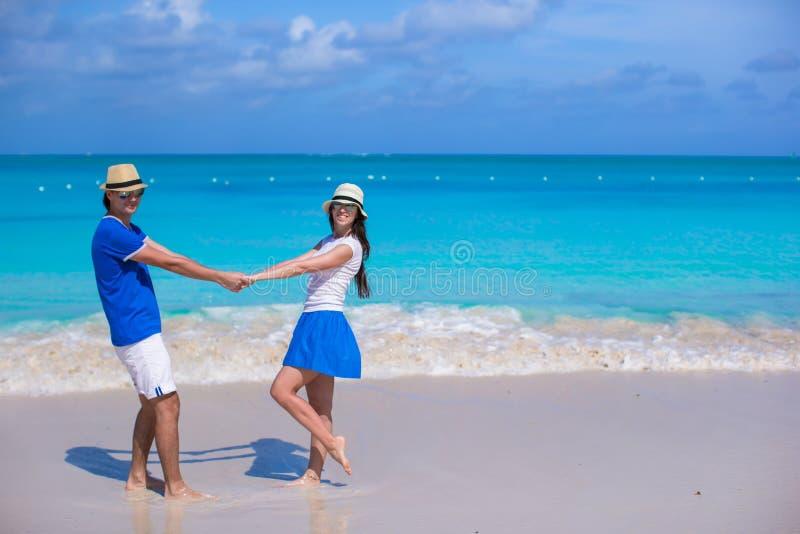 Los pares felices jovenes se divierten el vacaciones de la playa imagenes de archivo
