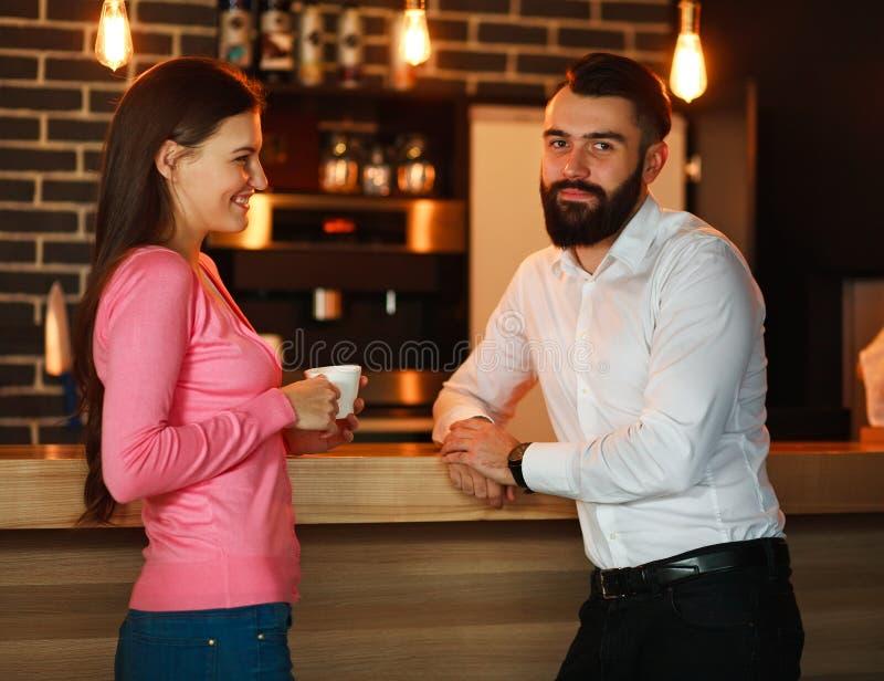 Los pares felices jovenes se encontraron en barra y hablar con la taza de café imagen de archivo