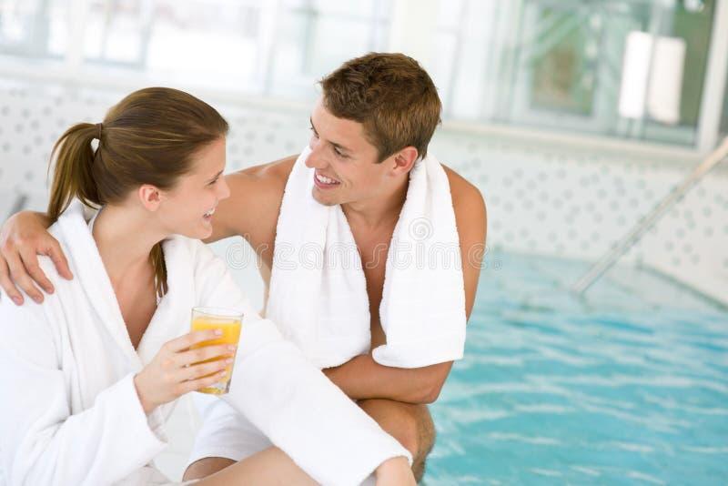 Los pares felices jovenes se relajan en la piscina fotografía de archivo