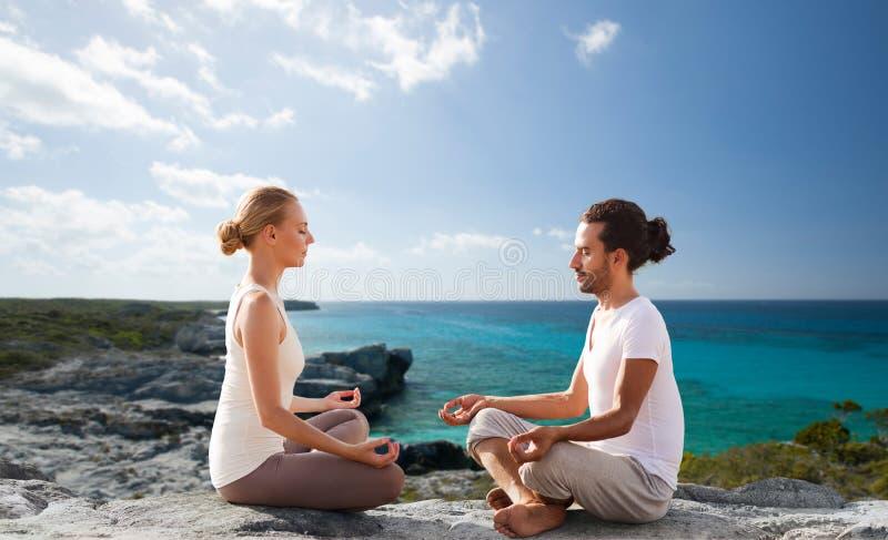 Los pares felices que meditan en loto presentan en la playa fotos de archivo