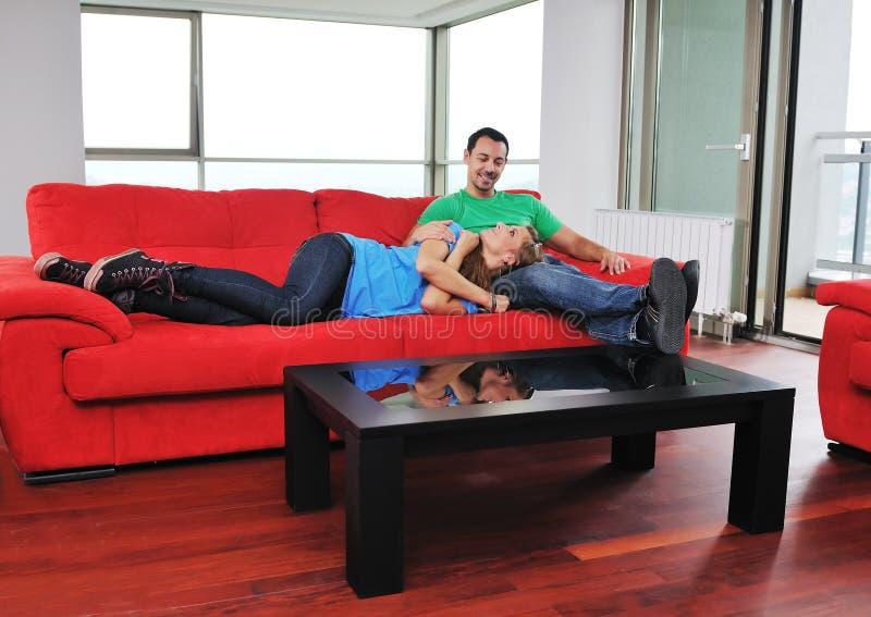 Los pares felices se relajan en el sofá rojo imagen de archivo