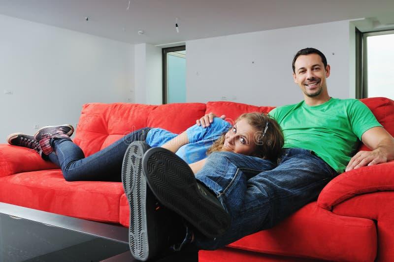 Los pares felices se relajan en el sofá rojo fotos de archivo
