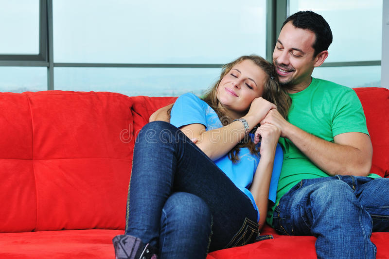 Los pares felices se relajan en el sofá rojo foto de archivo libre de regalías