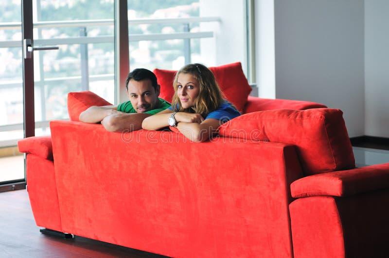 Los pares felices se relajan en el sofá rojo imagen de archivo libre de regalías