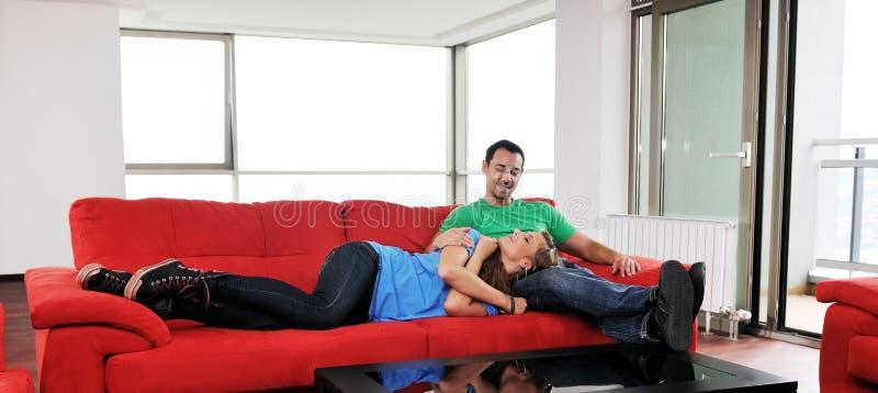 Los pares felices se relajan en el sofá rojo foto de archivo