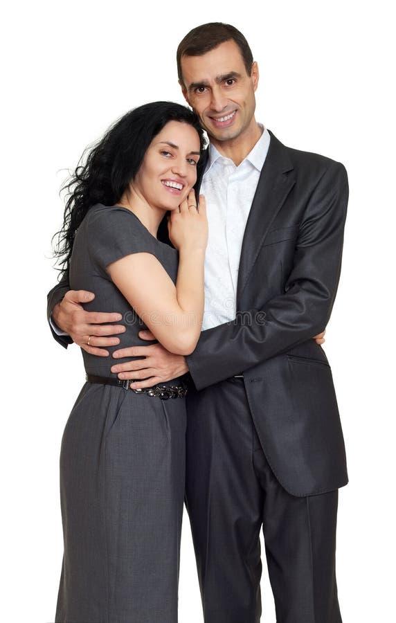 Los pares felices se vistieron en la ropa clásica, retrato en el estudio en blanco imagen de archivo libre de regalías