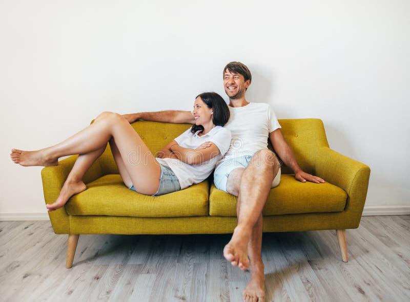 Los pares felices sonrientes en amor se divierten que se relaja en casa foto de archivo