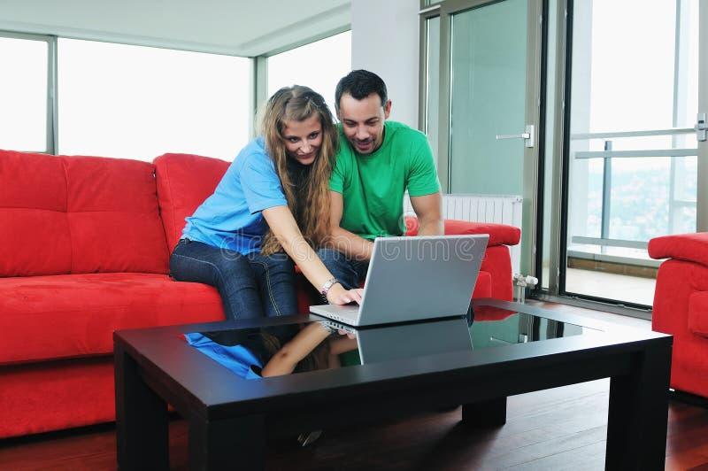 Los pares felices tienen la diversión y trabajo sobre la computadora portátil en casa imagenes de archivo