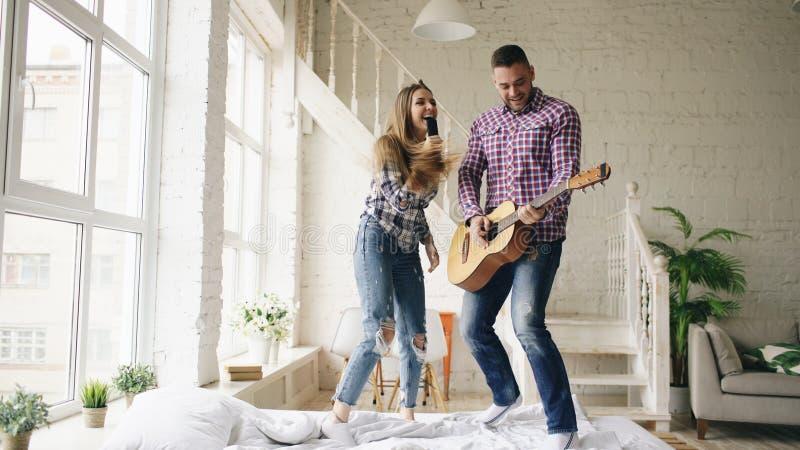 Los pares felices y cariñosos divertidos bailan en la cama que canta con el regulador de la TV y que toca la guitarra El hombre y imagen de archivo