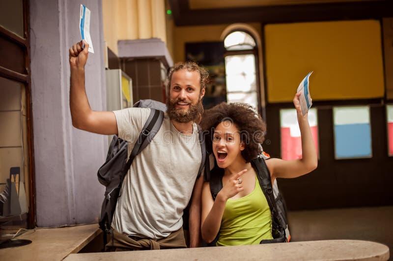 Los pares felices y eufóricos de los turistas del backpacker muestran los boletos FO fotografía de archivo