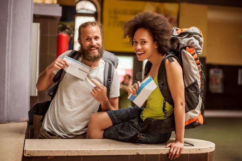 Los pares felices y eufóricos de los turistas del backpacker muestran los boletos FO foto de archivo