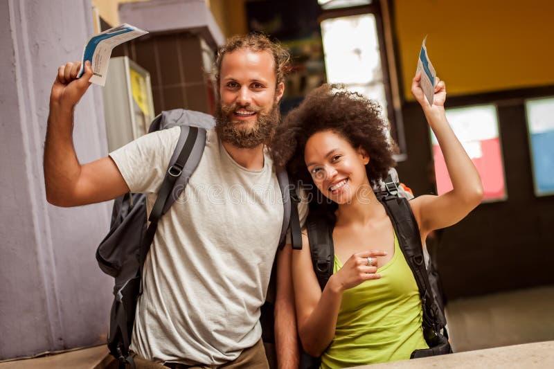 Los pares felices y eufóricos de los turistas del backpacker muestran los boletos FO fotos de archivo libres de regalías