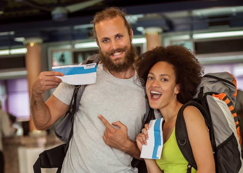 Los pares felices y eufóricos de los turistas del backpacker muestran los boletos FO fotografía de archivo libre de regalías