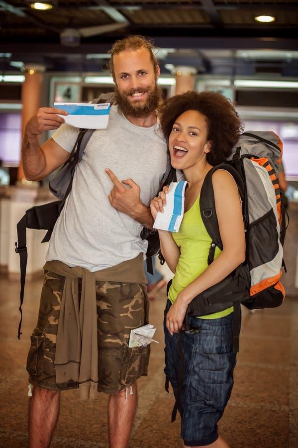 Los pares felices y eufóricos de los turistas del backpacker muestran los boletos FO imágenes de archivo libres de regalías
