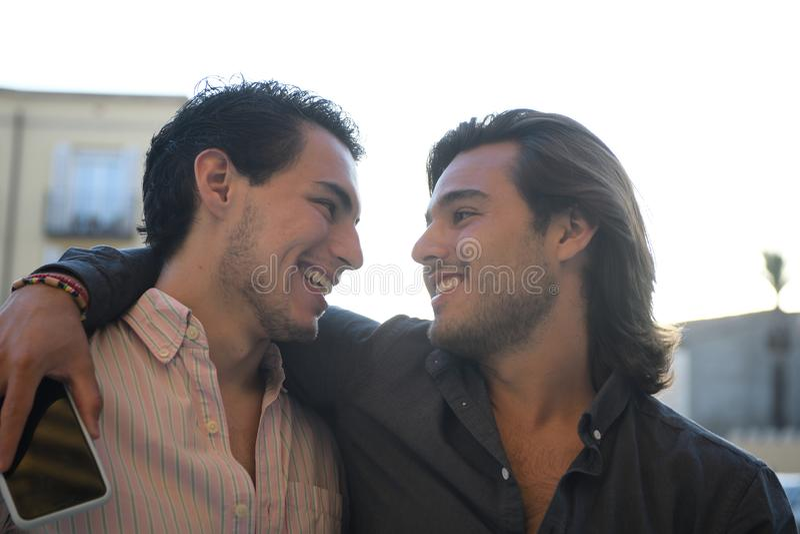 Los pares gay abrazaron y mirando de cerca imagen de archivo