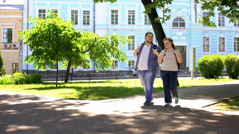 Los pares gordos del estudiante que caminan en ciudad parquean, fecha urbana, tiempo libre, amistad imagen de archivo