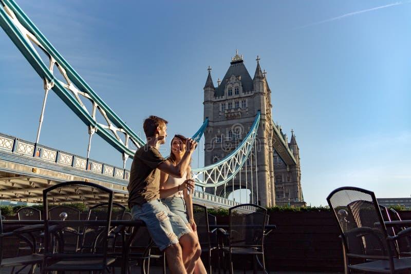 Los pares gozan del puente siguiente de la torre de la puesta del sol imagenes de archivo