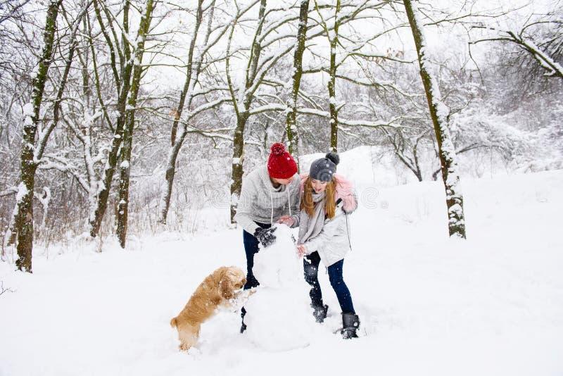 Los pares hacen el muñeco de nieve con un perro en bosque del invierno fotos de archivo libres de regalías