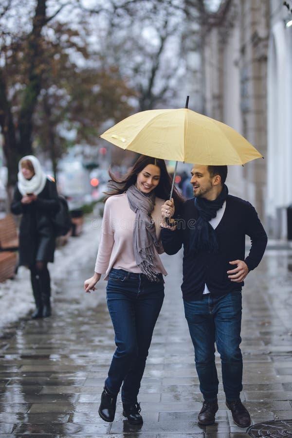 Los pares hermosos, el individuo y su novia vestidos en ropa casual están corriendo debajo del paraguas en la calle en imagen de archivo