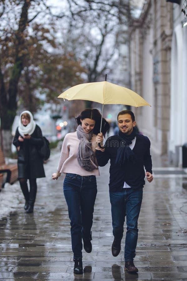 Los pares hermosos, el individuo y su novia vestidos en ropa casual están corriendo debajo del paraguas en la calle en imagen de archivo libre de regalías